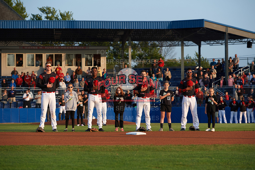 """Batavia Muckdogs Sean Reynolds (15), Demetrius Sims (55), Denis Karas (25), and Marcos Rivera (8) stand with the """"Stars of the Game"""" during the national anthem before a game against the Auburn Doubledays on August 26, 2017 at Dwyer Stadium in Batavia, New York.  Batavia defeated Auburn 5-4.  (Mike Janes/Four Seam Images)"""