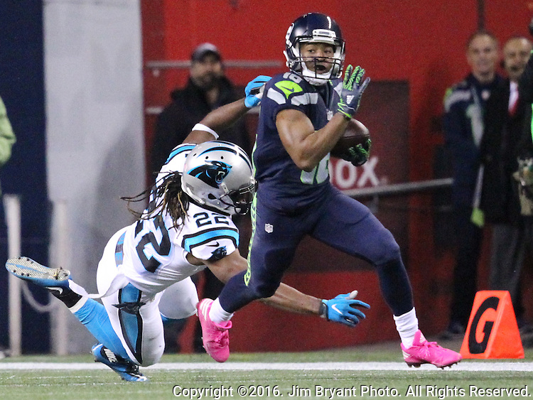 Seattle Seahawks wide receiver Tyler Lockett (16) runs past the  attempted tackle of Carolina Panthers free safety Michael Griffin (22) during a kickoff return at CenturyLink Field in Seattle, Washington on December 4, 2016.  Seahawks beat the Panthers 40-7. ©2016. Jim Bryant photo. All Rights Reserved.