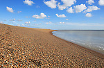 Steep beach profile sediment calm water blue sky white clouds landscape, Shingle Street, Suffolk, England, UK