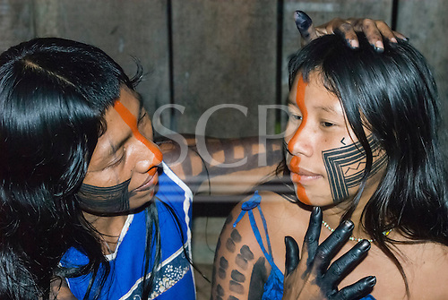 Mato Grosso State, Brazil. Aldeia Metuktire (Kayapo). Ngeiboro and Bekonire Metuktire applying genipapo and urucum face paint.