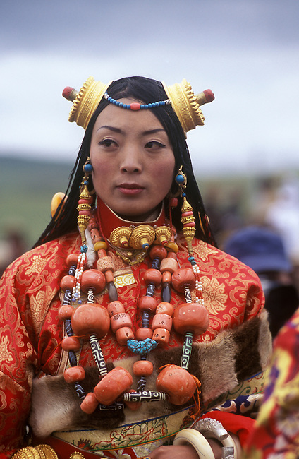 Female Khampa wears gold hair pieces & gau boxes, zee stones & coral at the Litang Horse Festival - Sichuan Province, China