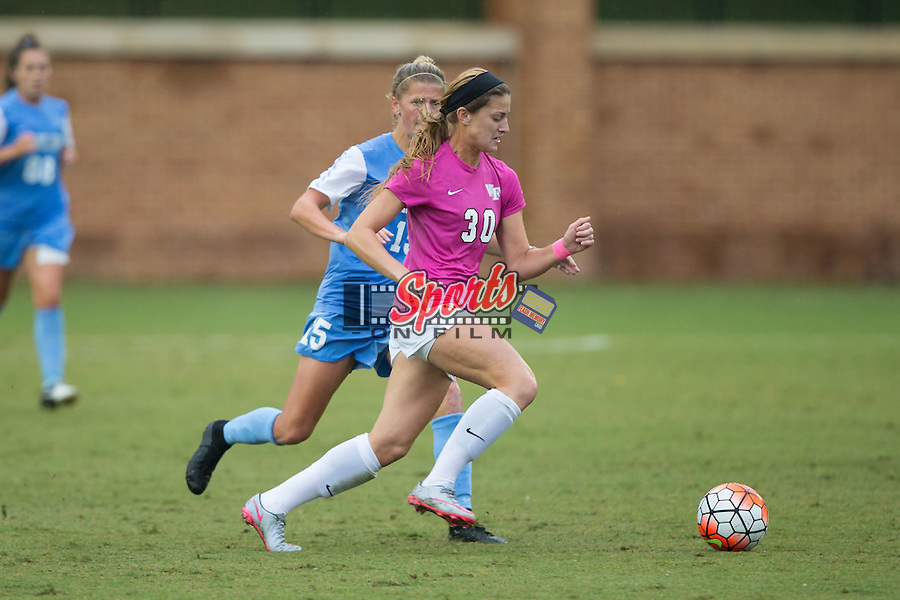 Sarah Medina (30) of the Wake Forest Demon Deacons looks to keep the ball away from Katie Bowen (15) of the North Carolina Tar Heels during first half action at Spry Soccer Stadium on September 27, 2015 in Winston-Salem, North Carolina.  The Tar Heels defeated the Demon Deacons 1-0.  (Brian Westerholt/Sports On Film)
