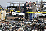 Comforted by neighbors, Jeannie Watts, left, stands outside the rubble where her mother June Hargis, 93, died in Thursday's brush fire in Pleasant Valley, south of Reno, Nev. Seen Saturday, Jan. 21, 2012, the family also lost their home, their barn and three horses.  (AP Photo/Cathleen Allison)