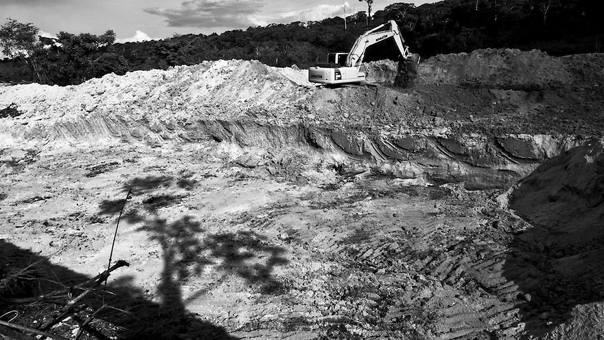 "Starting of hydraulic gold mining operation process known as ""chupadeira system"". Use of heavy machinery for excavation, workers clear the designated work front and then dug down to the level of ore-bearing material. Large and deep holes are made in forest land where gold miners will use high-pressure jets of water to dislodge rock material and move sediments. Amazon rain forest deforestation at Agua Branca gold mining village, Para State, Brazil."