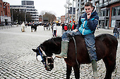 "Dublin, Ireland, January 2, 2011:.Boy sits on a horse and smokes a cigarette during the Smithfield horse market in central Dublin. This traditional market has now become a place for the young boys from poor northern neighborhoods of the city trade the horses, selling them for as little as 80 Euros, mistreating them and roaming on them up and down the slippery square..Since the beginning of crisis, between 10 and 20 thousand horses have become homeless or went in the hands of the youths in urban areas. Lots of Irish people who used to buy horses for fun during the boom years of ""Celtic Tiger"", now are abandoning them faced with expenditure of 35 Euro a week to properly maintain a horse. This animal previously worth 2000 Euro now can be purchased for as little as 80 Euro. New owners keep their horses in city greens, city ruins, or their house gardens, in very bad conditions. Most do not get much food, many are starving, dying, being mistreated..(Photo by Piotr Malecki / Napo Images)..Dublin, Irlandia, 2/01/2011:.Chlopak siedzi na koniu i pali papierosa podczas comiesiecznego targu koni w Smithfield w centrum Dublina..Ten tradycyjny targ  stal sie miejscem gdzie mlodzi chlopcy z biednych polnocnych dzielnic miasta handluja konmi po 80 euro, zle je traktujac i szalejac na nich po calym placu. .Od poczatku kryzysu od 10 do 20 tysiecy koni zostalo wyrzuconych na ulice przez wlascicieli nie chcacych placic okolo 35 Euro/tydzien za ich utrzymanie. Wpadaja one czesto w rece mlodziezy z ubogich dzielnic miasta, ktora handluje nimi, bije, glodzi, trzyma w skrajnie trudnych warunkach, w przydomowych ogrodkach lub ruinach budynkow i szaleje na nich po miescie. Kon, ktory byl wart 2000 Euro teraz moze byc kupiony za 80. .Fot: Piotr Malecki / Napo Images."
