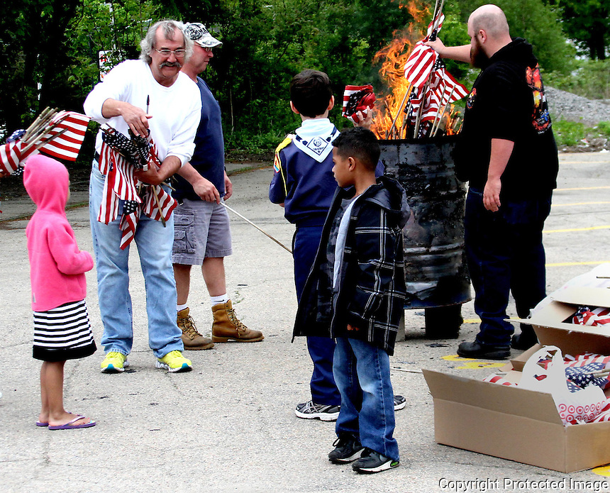 Volunteers reflag the graves of veterans interred at Holy Sepulcher and Evergreen Cemeteries in Stoughton Saturday, May 24 2014..<br /> (Photo by Gary Wilcox)