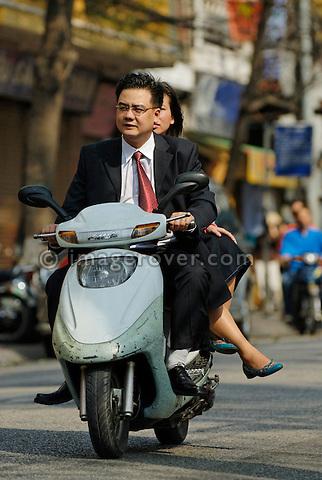 Asia, Vietnam, Hanoi. Hanoi old quarter. Smartly dressed vietnamese couple riding on a motorbike through Hanoi.