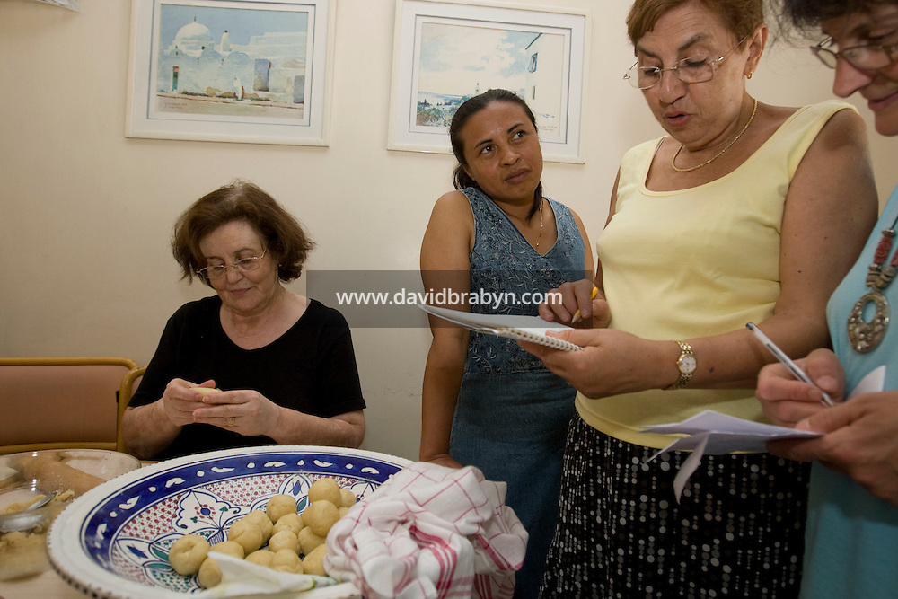Kethy Raobelina (3R), Nelly Sayagh (2R) and Mrs Chiche (R) compare recipes as Houria Guita (L) prepares Cornes de Gazelles during an Oriental pastry workshop held by the non-profit association Batisseusses de Paix (or Women Peace Builders) that seeks to build ties between Muslim and Jewish women, in a restaurant in Creteil, outside Paris, France, 24 June 2008.