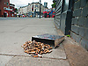 Cigarette end wall container spilt out on the pavement on a London street<br />