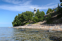 The Au Sable Light Station seen from the clear Lake Superior shoreline at Pictured Rocks National Lakeshore. Grand Marais, MI