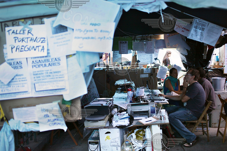 The interior of a tent, complete with computers, and printers. Signs and papers litter the walls inside and out. In May 2012, following a worsening financial crisis and a deepening recession in Spain, thousands of people started to gather in Spanish cities to protest against austerity, the global financial system, high unemplyment rate (Spain's is the highest rate in Europe) and the lack of opportunities. The protest movement has become known as 'los indignados' (the indignant ones).