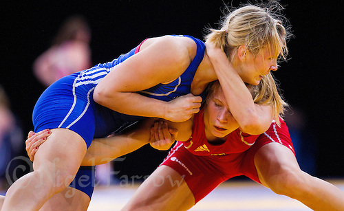11 DEC 2011 - LONDON, GBR - Aline Focten (GER) (in red) tries to overpower Laura Skujina (LAT) (in blue) during their women's 63kg category bronze medal bout during the London International Wrestling Invitational and 2012 Olympic Games test event  at the ExCel Exhibition Centre in London, Great Britain .(PHOTO (C) NIGEL FARROW)