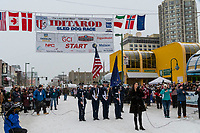 Pre Race Color Guard with singer and signers at 4th Avenue and D street in downtown Anchorage, Alaska on Saturday March 7th during the 2020 Iditarod race. Photo copyright by Cathy Hart Photography.com