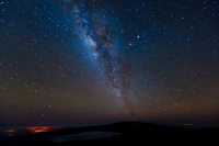 Night Lights: The Milky Way beams up over Mauna Loa, Big Island; on the left is the red glow of Halema'uma' Crater in Hawai'i Volcanoes National Park and the white glow of Hilo, Big Island, seen from Mauna Kea's summit.
