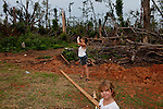 Amanda Porter takes photos of what will be her new home as her daughter Krista Holbooks, 5, stand nearby in Vaughn, Georgia August 12, 2011. In April, Vaughn was hit by a tornado that destroyed many homes in the area. Months later, the community is still picking up the pieces.