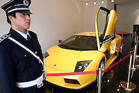 A security guard stands by the RMB3.98 millions (US$479,518) Murcielago at the first Lamborghini showroom in Beijing, China..