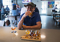 NWA Democrat-Gazette/CHARLIE KAIJO Sonephet Manivong of Grand Island, Neb. drinks a beer, Thursday, August 8, 2019 at the Bike Rack Brewing in Bentonville.<br /> <br /> Bike Rack Brewing is distributing into Little Rock now.