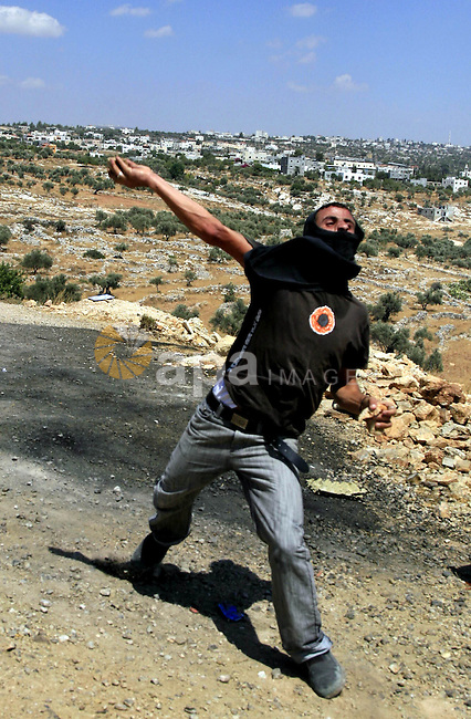 A Palestinian demonstrator throws a stone at Israeli soldiers as they fire teargas during a protest against the controversial Israeli separation barrier on July 31, 2009 in the West Bank village of Bilin near Ramallah. Israeli troops sprayed the protesters with contaminated water which induced vomiting; others had to be treated for the effects of tear gas inhalation. The non-violent Bilin demonstration occurs weekly, as villagers march to the separation wall after midday friday prayers. photo by Issam Rimawi