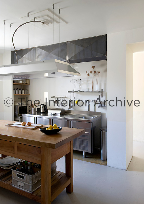 A large square light hangs over the wooden island in the centre of this stainless steel industrial-style kitchen