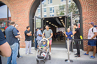 Apple enthusiasts leave the new Apple store in Williamsburg, Brooklyn in New York during the grand opening of their first store in Brooklyn on Saturday, July 30, 2016. The tech company's new store features exposed brick, giant arch windows and at one story with a brick facade blends in with the neighborhood. Apple gave away commemorative tee-shirts to those attending the grand opening. (© Richard B. Levine)