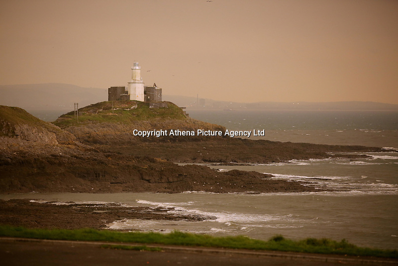 """Pictured: An unusually orange cloud over Mumbles Lighthouse at the seaside village of Mumbles near Swansea, UK. Monday 16 October 2017<br />Re: Remnants of Hurricane Ophelia are expected to bring strong gusts of wind to Wales when it hits Britain's shores.<br />The hurricane, making its way from the Azores in the Atlantic Ocean, will have weakened to a storm when it arrives.<br />A Met Office amber """"be prepared"""" warning has been issued in some areas bringing """"potential danger to life""""."""