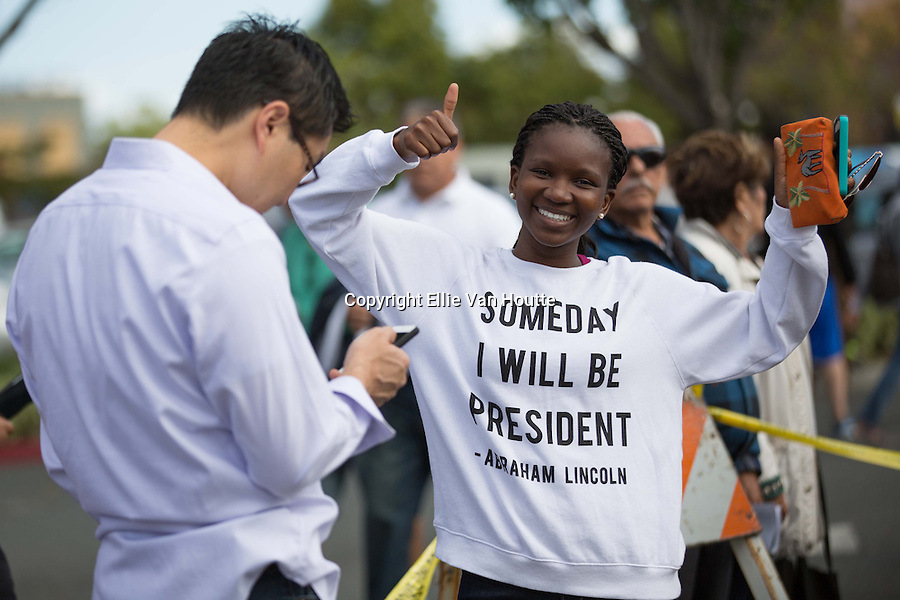 """Thabie Shabalala, who currently lives in Mountain View, CA, waited outside the police tape to see President Obama's motorcade after his speech at the Walmart Store in Mountain View.  As Shabala's shirt reads, """"Someday I will be president,"""" she intends to fulfill the dream to become the president of South Africa."""