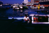 A sailor puts finishing touches painting his boat in the marina harbor.   Valparaiso port is a huge import/export site--for autos, copper, fruit and wine.  Boats in the port range from military boats and barges to small fishing and tourist boats. Valparaiso resembles a medieval European harbor more than a 20th century commercial port. Once a lively, wealthy seaport, Valpo was hurt when the Panama Canal opened.  It never recovered.