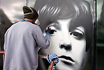 © Licensed to London News Pictures.  18/09/2017; Bristol, UK. VOYDER paints an image of Paul McCartney from The Beatles onto the front window of the Colston Hall. Colston Hall, Bristol's largest music venue, is to unveil a new mural painted in partnership with Upfest by Bristol artist Voyder of eight musical legends, each of which have performed at Colston Hall over the last 150 years, to celebrate the Colston Hall's 150th anniversary this week on 20 September.   The giant mural on the glass panes above the main entrance will feature portraits of Ella Fitzgerald, Louis Armstrong, David Bowie, Debbie Harry (Blondie), Jimi Hendrix, Mick Jagger, Sergei Rachmaninoff and Paul McCartney. The mural will be in place in time for Colston Hall to mark its anniversary with a big free Birthday Bash on Wednesday 20 September, exactly 150 years from when the venue first opened, to which all of Bristol is invited. Highlights for the night will include the world-famous Ukulele Orchestra of Great Britain, immersive projections from Limbic Cinema and toe tapping swing music from the Bruce/Ilett Big Band. The free event will begin at 6.30pm and see a complete takeover of the building, giving people the chance to explore every corner, stumbling across musicians, DJs, installations and projections, as acts pop up to create a unique party atmosphere. Colston Hall first opened its doors to the public on the 20th September 1867, after The Colston Hall Company bought the land from Colston Boy's School in 1861 to fulfil their vision of building a concert hall in the city. The Hall has seen four iterations in its 60 years, with the fourth and present Colston Hall opening in 1951. Picture credit : Simon Chapman/LNP