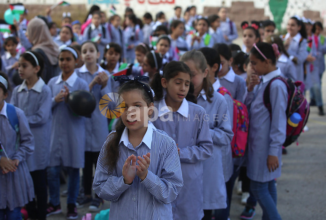 Palestinian schoolchildren stand in a line on the first day of a new school year, at a school in the West bank city of Nablus August 23, 2017. Photo by Ayman Ameen