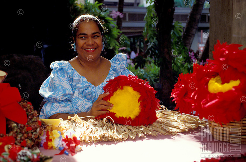 Local woman with red and yellow uli uli, feather gourd rattles, used for hula