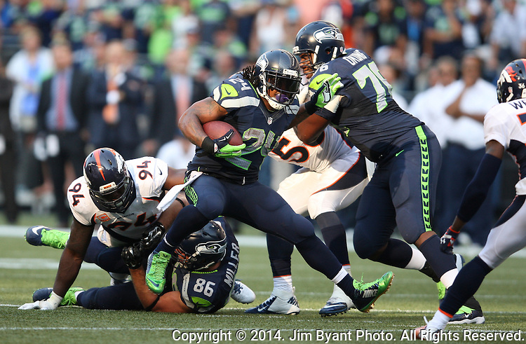 Seattle Seahawks running back Marshawn Lynch (24) looks for running room against  Denver Broncos in overtime at CenturyLink Field in Seattle, Washington on September 21, 2014.   Lynch ran for 88 yards and scored two touchdowns in the Seahawks 26-20 overtime win over the Broncos.  Providing blocking against the Broncos defenders is tackle Russell Okung (76)  and tight end Zach Miller (86)  ©2014. Jim Bryant Photo. All rights Reserved.