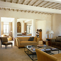 The main living area is furnished with contemporary sofas and chairs in shades of yellow and brown with a white travertine floor and whitewashed beamed ceiling