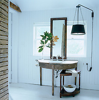In the master bathroom a semi-circular antique oak table has been transformed into a washstand and the large pendant light next to it is also a Darryl Carter design