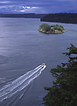 A small fishing boat cruises through Deception Pass between Whidbey island and Fidalgo island.