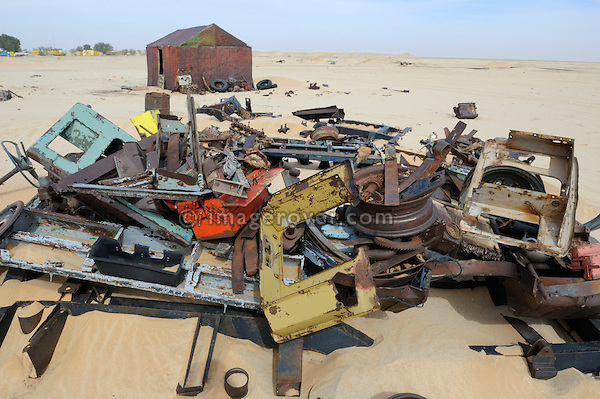 Africa, Mauritania, Sahara Desert. Various Land Rover parts buried in the Sahara sand next to a small village garage (shed in the background) located along the railroad track from Nouadhibou to Choum. --- No releases available. Automotive trademarks are the property of the trademark holder, authorization may be needed for some uses.