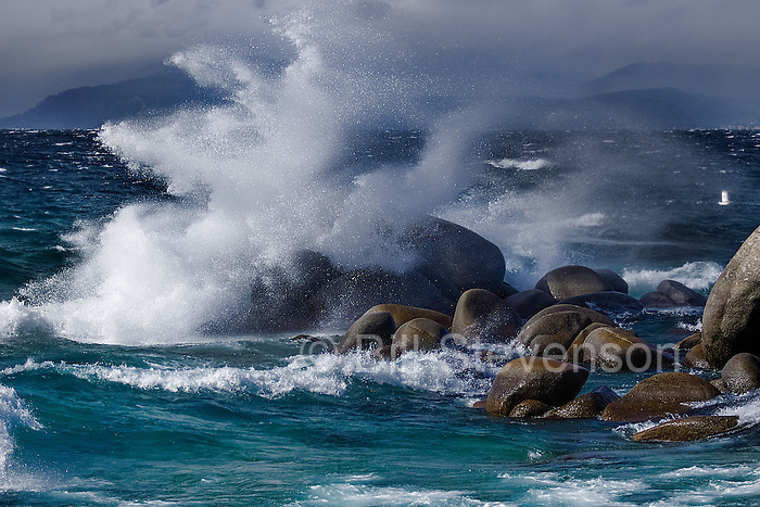 A winter wave crashing against the shore of Lake Tahoe