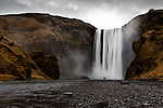 Two tourists bask in the mist of the mighty Skógarfoss waterfall on the South coast of Iceland under stormy skies.