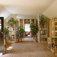 The brick-floored gallery and entrance hall is lined at one end with bookshelves