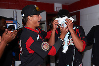 Batavia Muckdogs Jordan Holloway (left) pies starting pitcher Gabriel Castellanos in the locker room after Batavia defeated Mahoning Valley 1-0 on June 24, 2015 at Dwyer Stadium in Batavia, New York.  Castellanos, Brett Lilek and Steven Farnworth combined on a perfect game, the first in the teams 76 year history.  (Mike Janes/Four Seam Images)