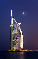Dubai.  Evening view  of Burj al Arab Hotel, architect W.S. Atkins, an icon of Dubai built in the shape of the sail of a dhow, stands on an island off Jumeirah Beach.  .