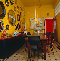 The wall of the yellow dining room is hung with antique mirrors