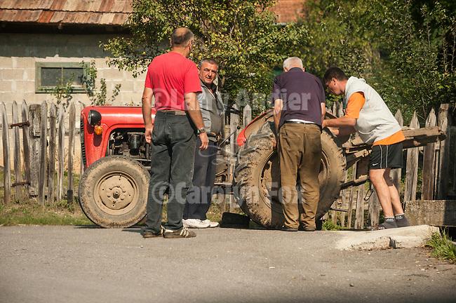 Men work on a tractor in Mokra Gora, Serbia