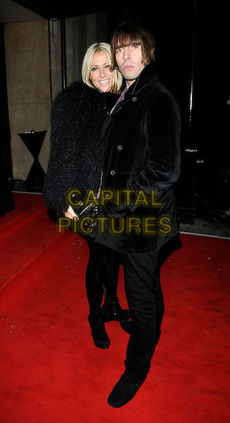 NICOLE APPLETON & LIAM GALLAGHER  .At the 20th Annual Drapers Awards, Grosvenor House, park Lane, .London, England, UK, .November 17th 2010..full length black coat fluffy tights dress jacket leather clutch bag wedges ankle boots couple married husband wife fur .CAP/CAN.©Can Nguyen/Capital Pictures.