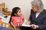 Researcher on home visit to three year old girl interacting with her and taking notes family is Mexican American researcher is causcasian New York City horizontal