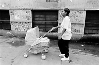 "USA. New York City. Spanish Harlem. Lady is 15 years old and is the single mother of Shana. She walks in the street with her child's stroller. Lady and her Puerto Rican family live below the poverty line and receives public assistance (AFDC, Home Relief, Supplemental Security Income and Medicaid). The family resides in units managed by the New York City Housing Authority (NYCHA) which provides housing for low income residents. NYCHA administers rental apartments in facilities, popularly known as ""projects"". Spanish Harlem, also known as El Barrio and East Harlem, is a low income neighborhood in Harlem area. Spanish Harlem is one of the largest predominantly Latino communities in New York City. 06.09.89 © 1989 Didier Ruef .."