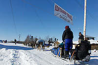 Karin Hendrickson passes under the checkpoint banner at the Shageluk village checkpoint during the 2011 Iditarod race..