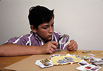 Berkeley CA Boy, twelve years old, engrossed in studyig his stamp collection with magnifying glass