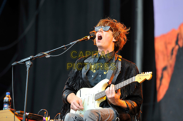 Blaine Harrison of The Mystery Jets.performing on Day 2 at Reading Festival, Reading, England. .25th August 2012.on stage in concert live gig performance performing music half length black fringed jacket sunglasses shades guitar singing .CAP/MAR.© Martin Harris/Capital Pictures.