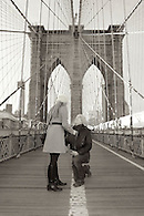 Sepia toned image of wedding proposal on Brooklyn Bridge with the iconic stone arches in the background.