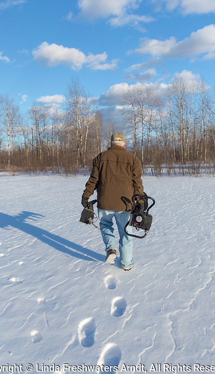 Ice fisherman carrying a fish locator in one hand and an ice auger in the other.